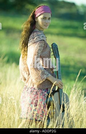 Jungen Hippie-Frau Wandern durch Feld, halten Gitarre - Stockfoto