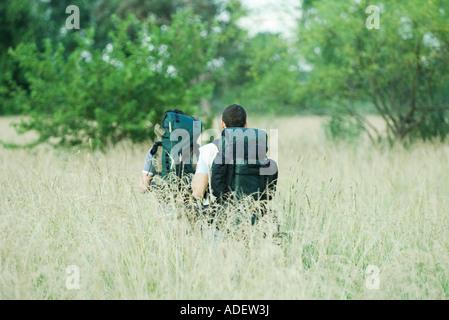 Zwei Wanderer zu Fuß durch Feld, Rückansicht - Stockfoto