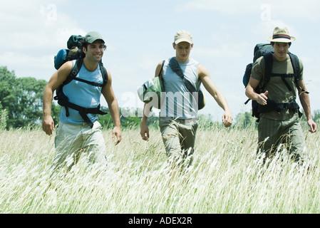 Drei Wanderer zu Fuß durch Feld - Stockfoto