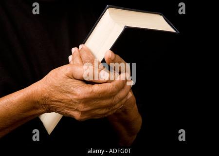 Eine alte Frau hält eine Bibel im Gebet - Stockfoto