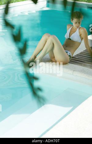 Junge Frau sitzt Pool, in voller Länge - Stockfoto