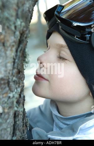 Junge schiefen Gesicht nah an Baum, Augen geschlossen - Stockfoto
