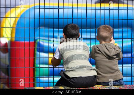 zwei jungen Durchsicht Drahtzaun auf Hüpfburg im fun-Park Fokus auf jungen - Stockfoto
