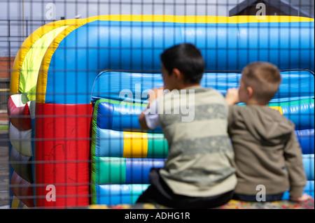 zwei jungen Durchsicht Drahtzaun auf Hüpfburg im fun Park Fokus auf Hüpfburg - Stockfoto