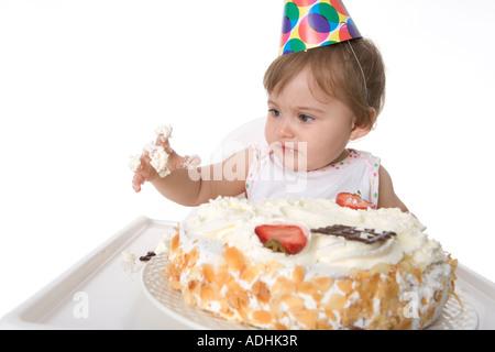 Einjähriges Mädchen von ihrem Geburtstagskuchen Essen - Stockfoto