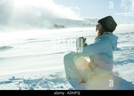Teen Mädchen sitzen im Schnee Hände mit geschlossenen Augen - Stockfoto