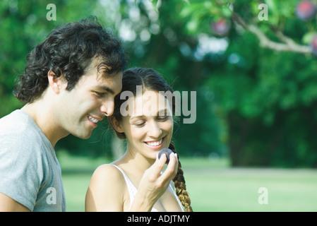 Stand in der Nähe Pflaumenbaum, Pflaume hält Frau paar - Stockfoto