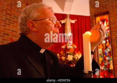 EIN KATHOLISCHER PRIESTER BLÄST EINE KERZE IN EINER KAPELLE UK 2005 - Stockfoto
