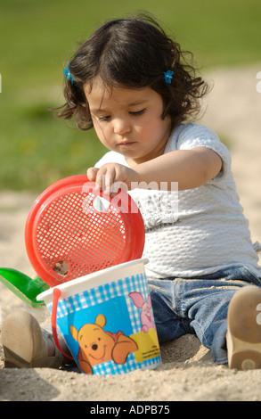 Kleine Mädchen spielen mit sand - Stockfoto
