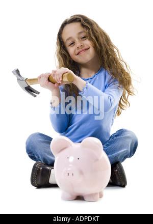 Schneidersitz sitzen mit Hammer und Sparschwein lächelnde Mädchen - Stockfoto