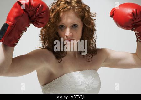 Frau im Hochzeitskleid mit Boxhandschuhen - Stockfoto