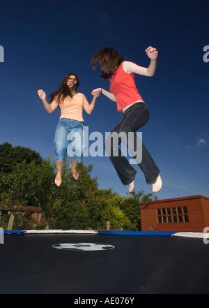 zwei junge Frauen auf Trampolin springen - Stockfoto