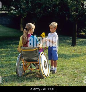 Kleiner junge behinderte Frau im Rollstuhl im Garten Blumen verleihen - Stockfoto