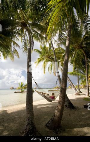 Mädchen in einer Hängematte im Schatten der Palmen auf der tropischen Insel Manihi auf den Tuamotu-Inseln von Französisch - Stockfoto