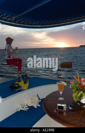 Junge Frau beobachtet den Sonnenuntergang auf einem Luxus-Katamaran in den Gewässern um die Fidschi-Inseln im Südpazifik - Stockfoto