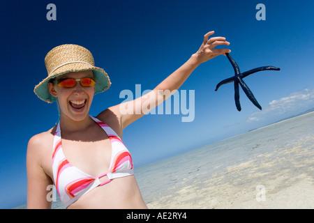 Mädchen im Bikini hält einen Seestern auf einer Sandbank in einer tropischen Lagune in Fidschi-Inseln im Südpazifik - Stockfoto