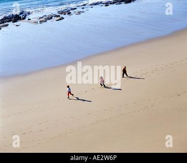 drei Kinder laufen an einem Strand neben den Wasser-s-Rand - Stockfoto
