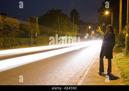 eine Frau stand neben einer Straße in der Nacht mit Durchgangsverkehr - Stockfoto
