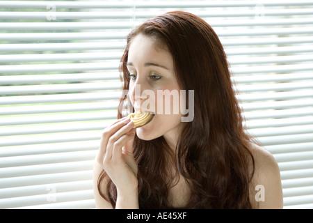 Eine junge Frau Essen Schokoladenkekse - Stockfoto
