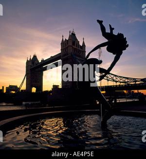 Brunnenskulptur Statue des Mädchens mit Delphin und der Tower Bridge im Sonnenuntergang Silhouette London EC3 E1 - Stockfoto