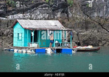 Junge steht auf der Veranda des einsamen Fishermans Haus am schwimmenden Fischerdorf Halong Bucht Vietnam - Stockfoto