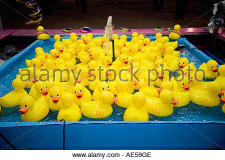 Gelbes Kautschuk Enten am Karneval Ring Toss Spiel, das ein Spiel des Zufalls und Geschick Ihre Enten in einer Reihe - Stockfoto