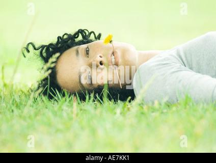 Frau liegt auf dem Rasen mit Löwenzahn im Mund - Stockfoto