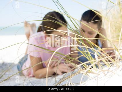 Zwei Mädchen im Teenageralter liegen am Strand, gesehen durch Dünengras - Stockfoto