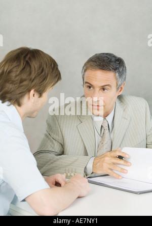 Junger Mann mit reifer Geschäftsmann, Dokument diskutieren - Stockfoto