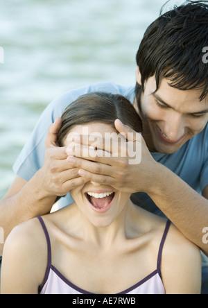 Junger Mann für seine Freundin Augen, beide lachen, Porträt, Nahaufnahme - Stockfoto