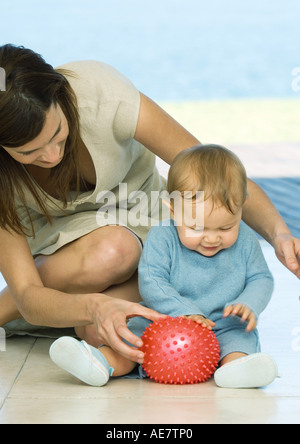 Frau sitzt auf dem Boden spielen mit baby - Stockfoto