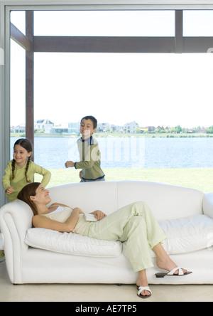 Mutter auf Sofa liegend, während Kinder um sie herum laufen - Stockfoto
