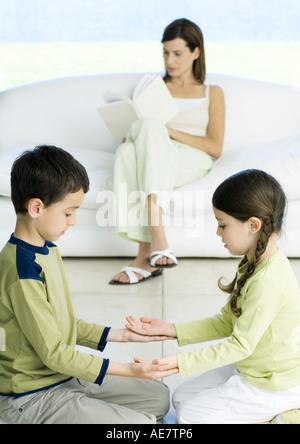 Jungen und Mädchen spielen, während Mutter im Hintergrund liest - Stockfoto
