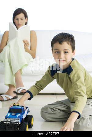 Jungen spielen mit Spielzeug-Auto, während Mutter im Hintergrund liest - Stockfoto