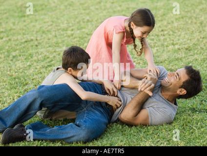 Jungen und Mädchen kitzeln Vater auf Rasen - Stockfoto