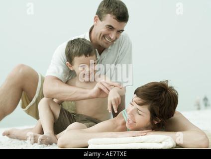 Familie am Strand, Mann und Sohn stört Frau während sie liegen - Stockfoto