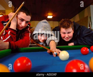 DREI JUNGS IM TEENAGERALTER BILLARD SPIELEN, IN DER JUGEND CLUB UK - Stockfoto