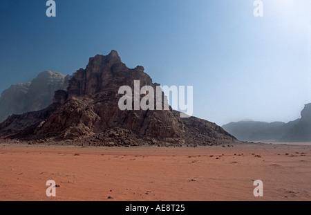 Roten Sandboden der Wüste mit Felsvorsprüngen genannt Jebels in der Ferne Wadi Rum Jordan Travelling auf Kamelen - Stockfoto