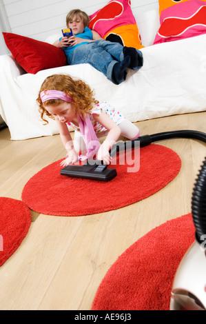 2 Kinder zu Hause, kleines Mädchen saugen, wenig junge sitzt auf einem sofa - Stockfoto