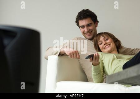 Lächeln, paar liegend auf dem Sofa vor dem Fernseher - Stockfoto