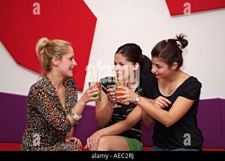 Drei junge Frauen in einer Bar in einer Nacht erhöhen ihre Gläser in einem Toast - Stockfoto