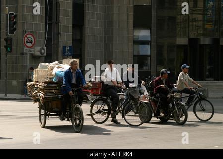 Radfahrer an der Ampel. Pedal powered Transport schweren Gütern und Personen ist nach wie vor erhebliche in Shanghai - Stockfoto