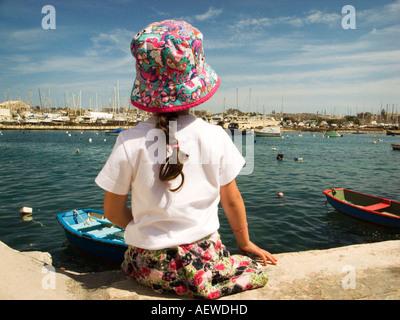 Rückansicht des Kind 4-5 Jahre alt in bunten hat das Meer bewundern, St. Paul's Bay, Malta - Stockfoto