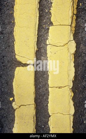 Detail aus direkt oberhalb von gerissenen und blass gelbe Doppellinien übermalt viermal auf getragen graue Asphaltstraße - Stockfoto