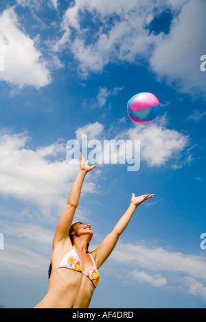 Junge Frau im Bikini am Strand vor einem hellen aber bewölkten Sommerhimmel fängt einen Ball. Strandbad Wannsee, - Stockfoto