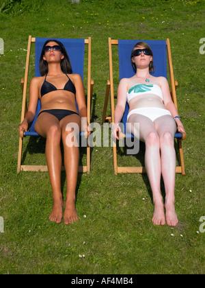 Zwei Mädchen Sonnenbaden In Liegestühlen ist eine gegerbt ist blass - Stockfoto