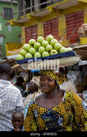 Nigeria Lagos Mitte Erwachsene Frau Apfel auf dem Marktplatz zu verkaufen - Stockfoto
