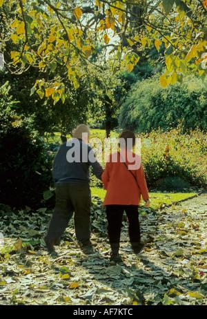 älteres Ehepaar genießen Sie einen gemütlichen Spaziergang in der Herbstsonne baumbeschatteten Wald West Dean Gardens - Stockfoto