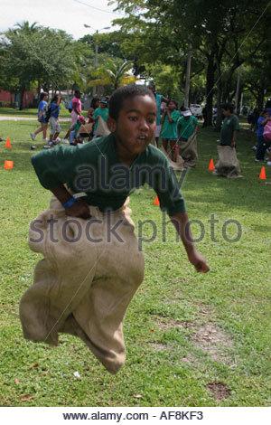 Miami Florida Hadley Park Miami Dade County Parks Sommer Camp Programm Kartoffelsack Rennen schwarzen Jungen springen - Stockfoto