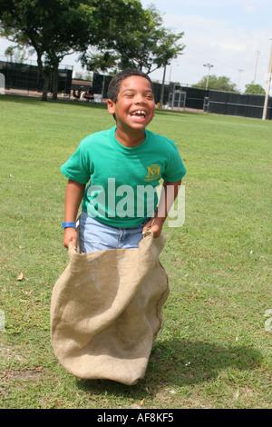 Miami Florida Hadley Park Miami Dade County Parks Sommer Camp Programm Kartoffelsack race Black boy - Stockfoto